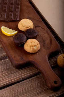 Side view of muffins with lemon slice and dark chocolate on a wooden cutting board