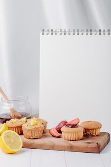 Боковой вид кексы с клубникой и лимоном на доске с банкой варенья и белой тетрадью