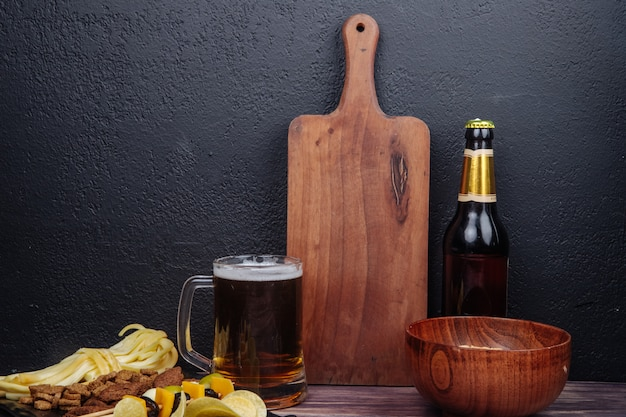 Side view of a mug of beer with a wood cutting board bottle of beer and various salty snacks on black