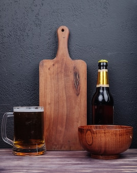 Side view of a mug of beer with a wood cutting board bottle of beer and wood bowl on black