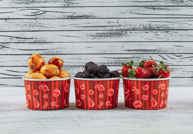 Side view mulberries in bowls with loquats and strawberries on light wooden background. horizontal free space for your text