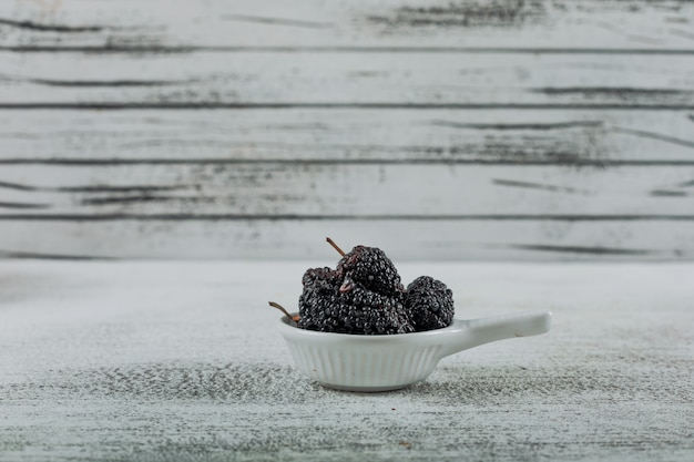 Side view mulberries in small bowl on light wooden background. horizontal free space for your text