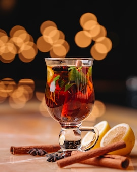 Side view of mulled wine with cinnamon anise and orange in a glass on the table on dark background