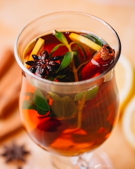 Side view of mulled wine with cinnamon anise and orange in a glass