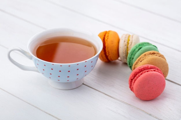 Side view of multi-colored macarons with a cup of tea on a white surface