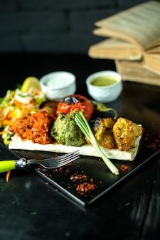 Вид сбоку разноцветные фрикадельки с помидорами и соусами и зеленым луком