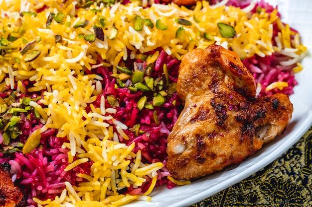 Вид сбоку разноцветный рис с жареным куриным крылышком и тыквенными семечками сверху