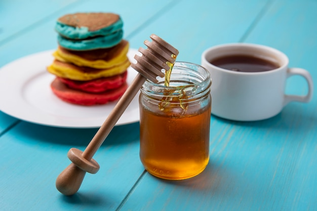 Side view multicolored pancakes on a plate with honey in a jar and a wooden honey spoon with a cup of tea on a turquoise background