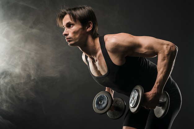 Side view of muscled man holding weights