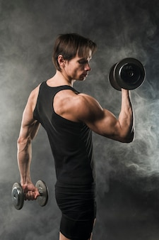 Side view of muscly athletic man holding weights