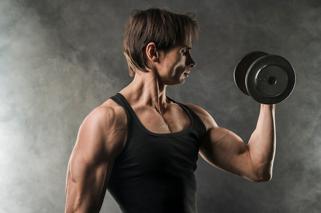 Side view of muscly man holding weight