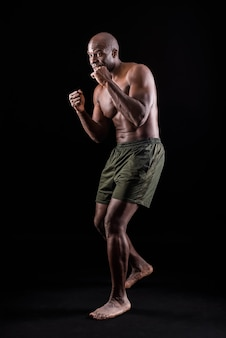 Side view of a muscular adult male standing in defensive boxing pose on a black background