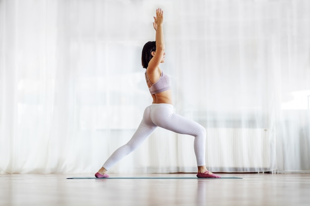Side view of muscular fit attractive brunette with short hair standing in crescent lunge yoga position. yoga studio interior.