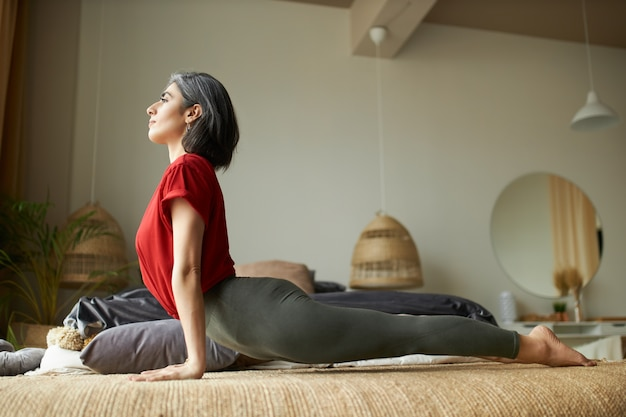 Side view of muscular fit young gray haired woman practicing yoga in bedroom, doing upward facing dog pose