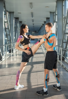 Side view of muscular flexible brunette woman practicing split, holding leg on shoulder of man