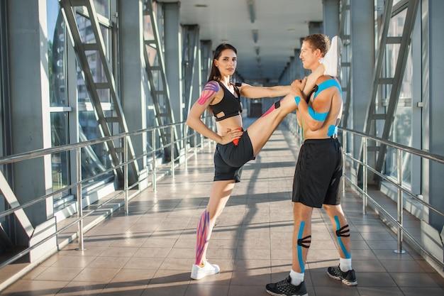 Side view of muscular flexible brunette woman practicing split