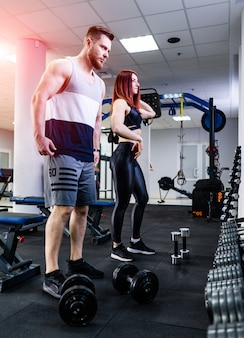 Side view of muscular man and a woman in the modern gym. beardy bodybuilder and red-haired female standing