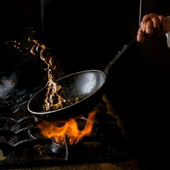 Side view mushroom frying with gas stove and fire and human hand in pan