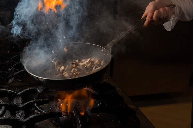 Side view mushroom frying with smoke and fire and human hand and pan in stove