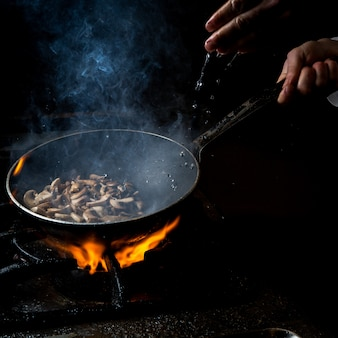 Side view mushroom frying with water drop and fire and human hand in pan