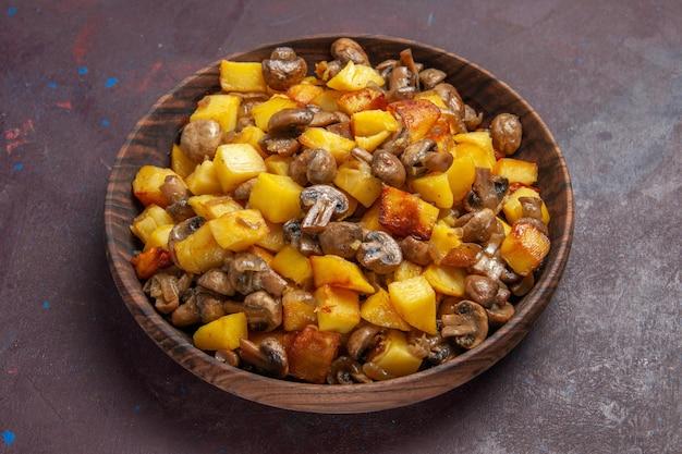 Vista laterale funghi con patate in mezzo allo sfondo scuro ci sono patate fritte con funghi in una ciotola marrone su sfondo viola