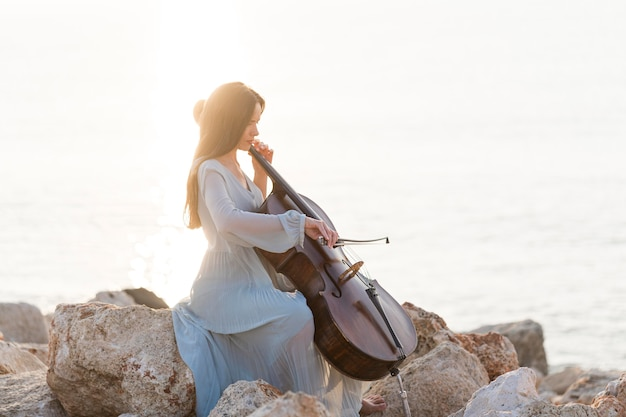 Side view of musician playing cello on rocks by the sea