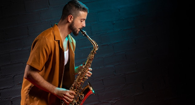 Side view of musician playing the saxophone in spotlight with copy space