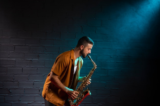 Side view of musician playing the saxophone in spotlight