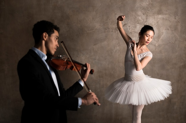 Side view of musician playing violin and ballerina dancing