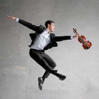 Side view of musician posing mid-air while holding violin