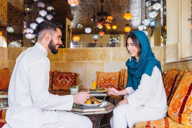 Side view of muslim couple in arab restaurant