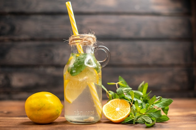 Side view of natural fresh detox water served with tube mint and orange on a brown background
