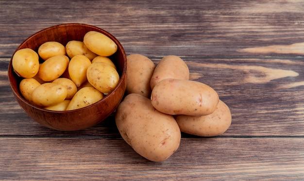 Vista laterale delle patate novelle in ciotola e quelle bianche sulla tavola di legno con lo spazio della copia