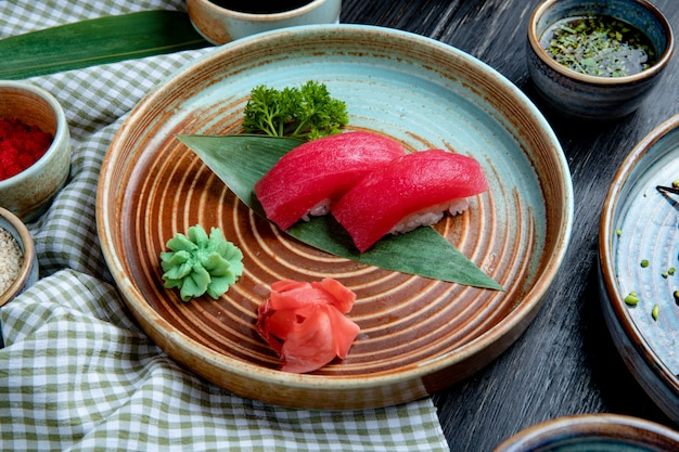 Side view of nigiri sushi with tuna on bamboo leaf served with pickled ginger slices and wasabi on a plate