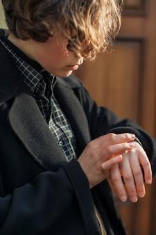 Вид сбоку небинарный человек, смотрящий на часы