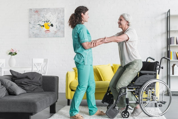 Side view of nurse holding senior woman patient's hand standing from wheel chair