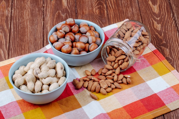 Side view of nuts peanuts hazelnuts in bowls and almond scattered from a glass jar on plaid table napkin on wooden background