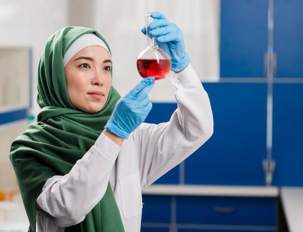 Scienziata femminile di vista laterale o con hijab in laboratorio che esamina sostanza