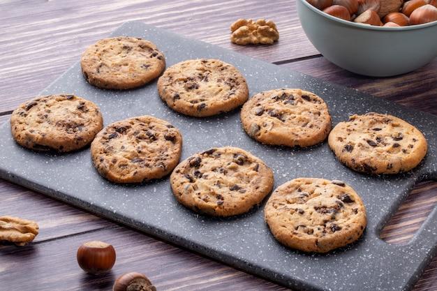 Biscotti di farina d'avena di vista laterale con cioccolato su un bordo con le noci
