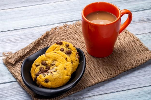 Side view of oatmeal cookies with chocolate chips and a mug with cocoa drink on a wooden