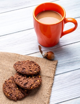 Side view of oatmeal cookies with chocolate chips and nuts and a mug with cocoa drink on a wooden