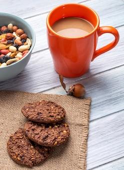 Vista laterale dei biscotti di farina d'avena con le gocce di cioccolato e le noci con una tazza della bevanda del cacao su un di legno