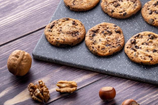Вид сбоку овсяное печенье с шоколадом на доске с орехами