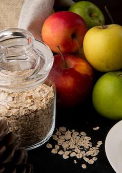 Вид сбоку овсянки в стеклянной банке с цветными яблоками на столе