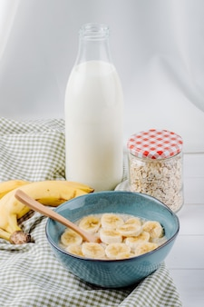 Vista laterale del porridge di farina d'avena con banana in una ciotola in ceramica e una bottiglia di vetro di latte sul tavolo rustico