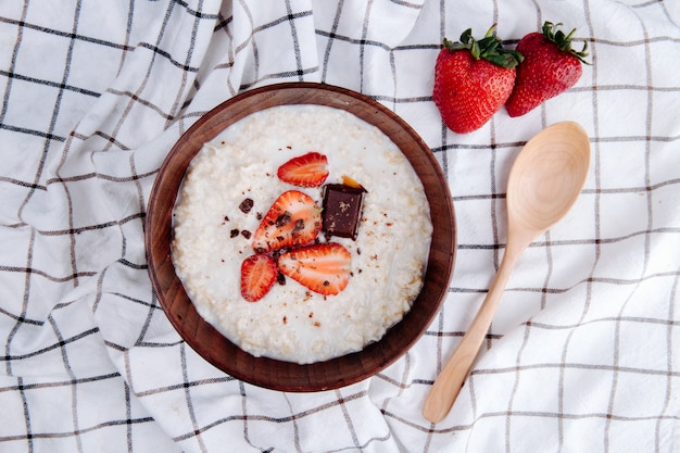 Side view of oatmeal porridge with fresh ripe strawberries and chocolate in a wood bowl and a spoon on plaid fabric