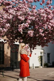 Вид сбоку красивой белокурой модели девушки в солнечных очках и красном пальто, позирующей возле розового цветущего дерева и смотрящей в камеру.