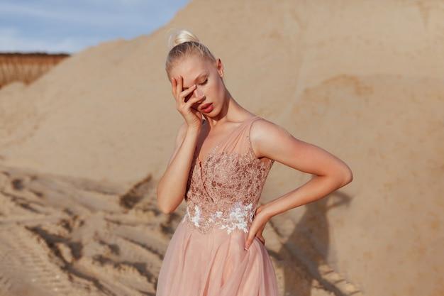 Вид сбоку красивой молодой женщины, позирующей в пустыне, с закрытыми глазами, закрыла лицо рукой. красивый теплый закатный свет.