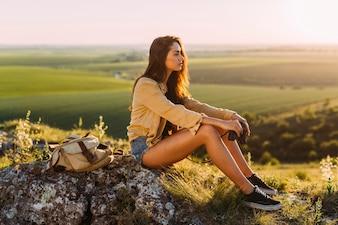美しい若い女性の岩の上に座っているの側面図