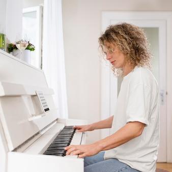 Блондинка играет на пианино, вид сбоку